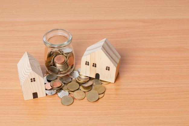 Geldmunten besparen met een houten huismodel op een houten achtergrond. concept voor de aankoop van een woning.