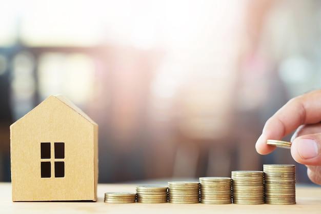 Geldmunten op elkaar gestapeld in verschillende posities en huis in bruin gerecycled papieren model op de houten tafel.