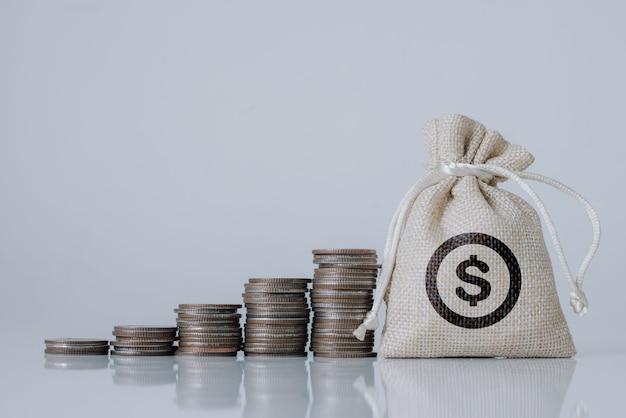 Geldzak en stapelen van gouden munten met opgroeien op de witte houten in de studio voor leningen aan geplande investeringen in het toekomstige concept.