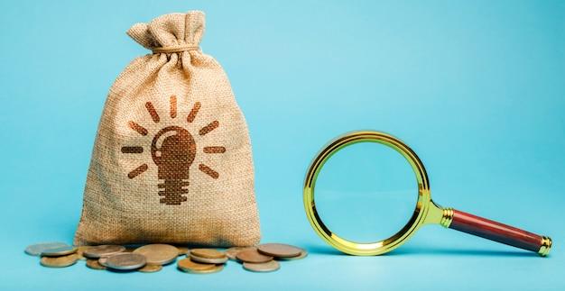 Geldzak met symbool gloeilamp idee en vergrootglas. genereren van innovatieve zakelijke ideeën.