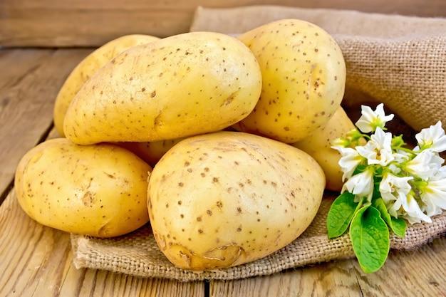 Gele aardappelknollen met een bloem bij het ontslaan op houten planken
