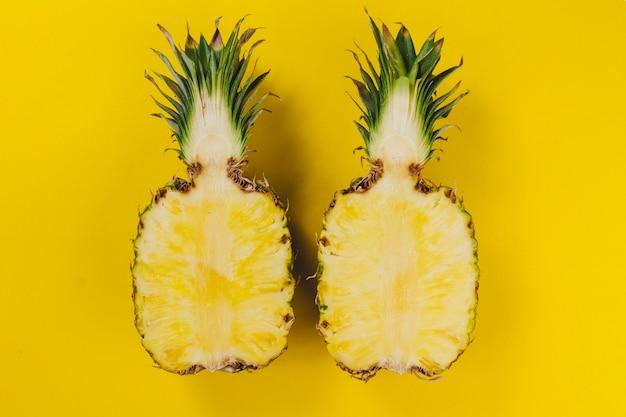 Gele achtergrond met ananas gesneden in de helft