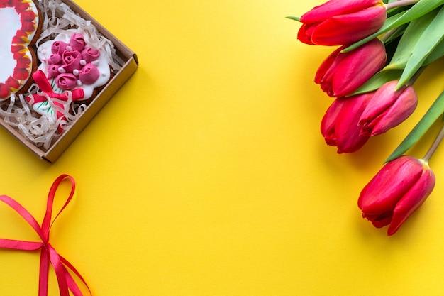 Gele achtergrond met een doos met decoratieve koekjes en rode tulpen, sjabloon voor tekst