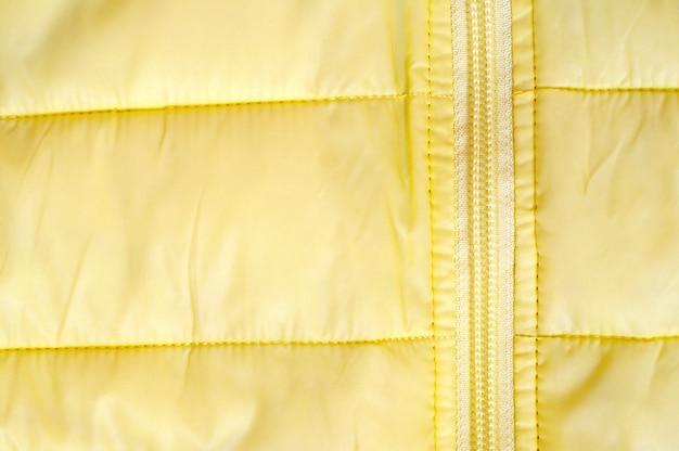 Gele achtergrond met fragment jas en zip