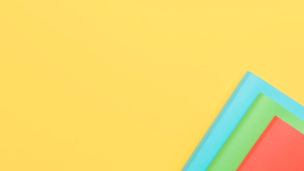 Gele achtergrond met vellen papier in de hoek