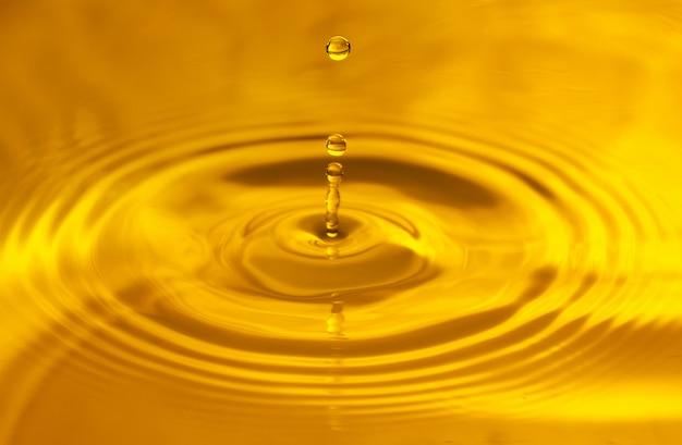 Gele achtergrond, textuur. druppels vallen in water en cirkels lopen op water, met reflectie