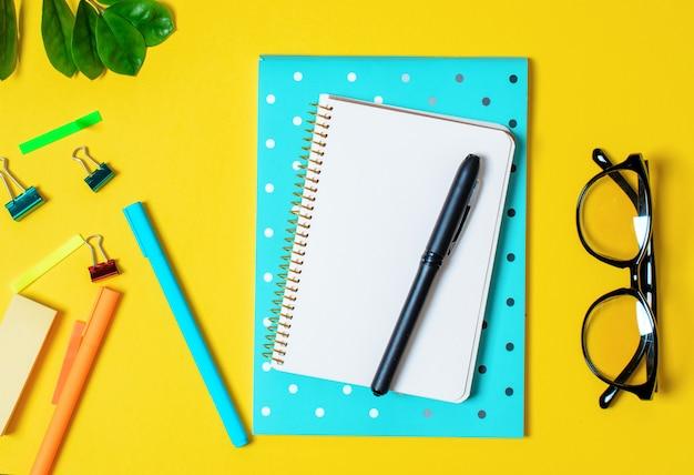 Gele achtergrond, wit notitieboekje voor records, telefoon, computerbril, takjesplanten,
