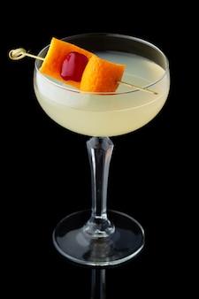 Gele alcoholcocktail met munt en sinaasappelschil die op zwarte achtergrond wordt geïsoleerd