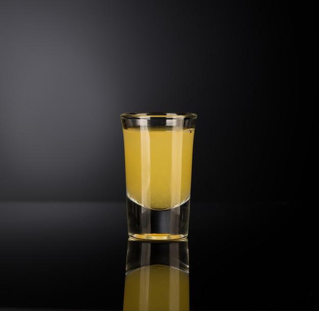 Gele alcoholische drank in een borrelglas geïsoleerd op een donkere achtergrond met achtergrondverlichting