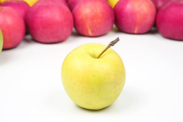 Gele appel op een achtergrond van rode appels op een witte achtergrond. vitamine en gezonde voeding