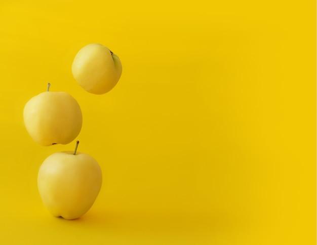Gele appels op een gele achtergrond in zwaartekracht. helder, sappig zwart-wit fruit