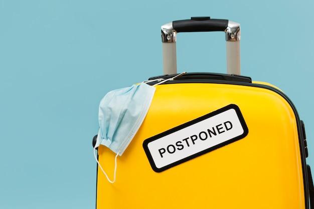 Gele bagage met uitgesteld teken en medisch masker