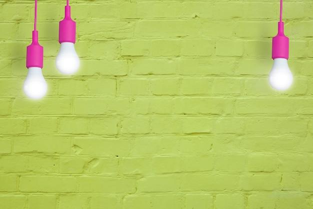 Gele bakstenen muur met gloeilampen creatieve kopieerruimte voor uw tekst of afbeelding