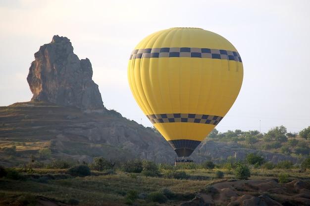Gele ballon met mensen die dichtbij de rots vliegen