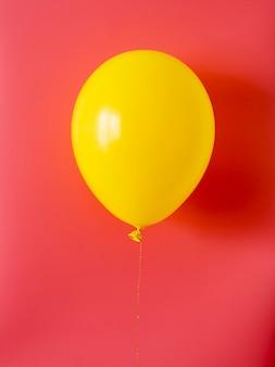 Gele ballon op rode achtergrond