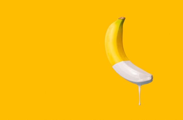 Gele banaan met grijze verf die eruit druipt. minimalistisch concept met kopie ruimte