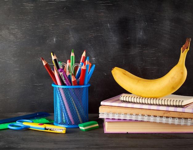 Gele banaan op een stapel notebooks, een blauw briefpapierglas met veelkleurige houten potloden
