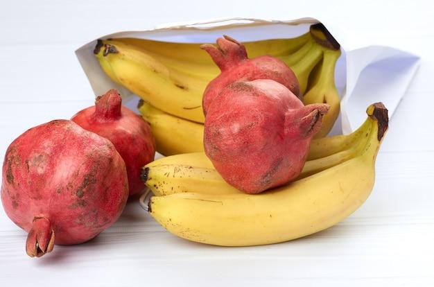 Gele bananen en rijpe rode granaatappels op een witte marmeren tafel, close-up