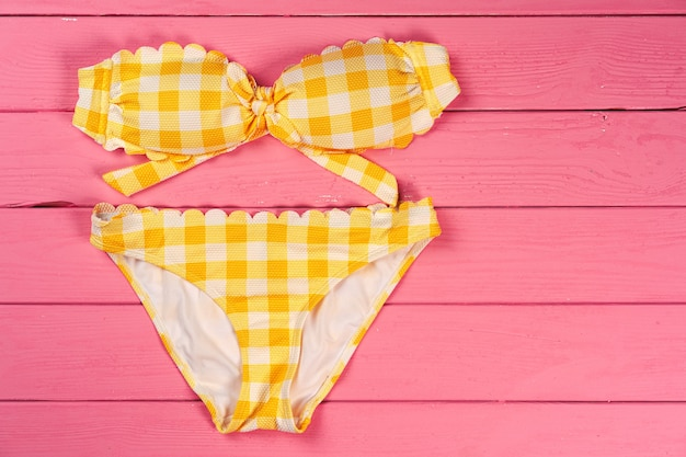 Gele bikini op felroze houten