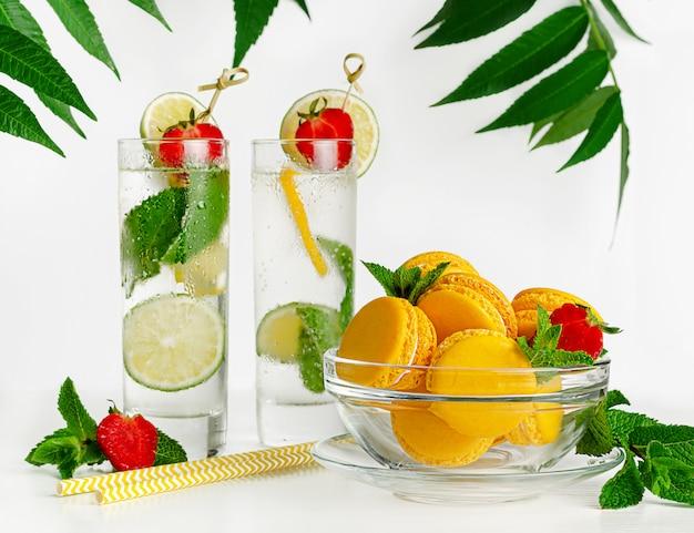 Gele bitterkoekjes en limonade met limoen, munt en aardbeien op wit. kopieer ruimte
