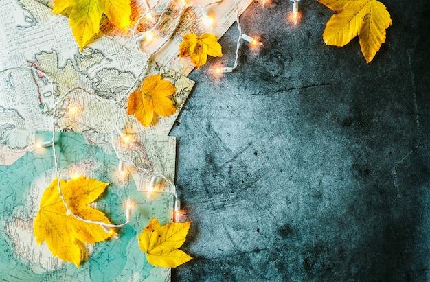 Gele bladeren geografische kaart en gloeiende slinger op een betonnen achtergrond