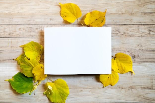 Gele bladeren herfst houten achtergrond wit blanco papier kopie ruimtekleurige kleurrijke mock up