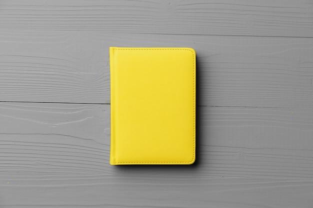 Gele blocnote op grijze houten hoogste mening als achtergrond, exemplaarruimte