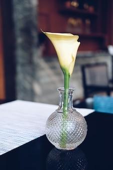 Gele bloem in glasvaas op restaurantlijst