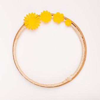 Gele bloemen die op cirkelvormig houten frame op witte achtergrond worden verfraaid