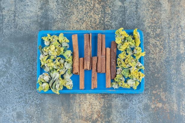 Gele bloemen en kaneelstokjes op blauw bord.