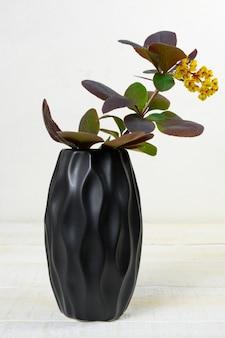 Gele bloemen in een zwarte vaas op een witte houten tafel