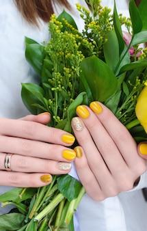 Gele bloemen in vrouwenhanden.