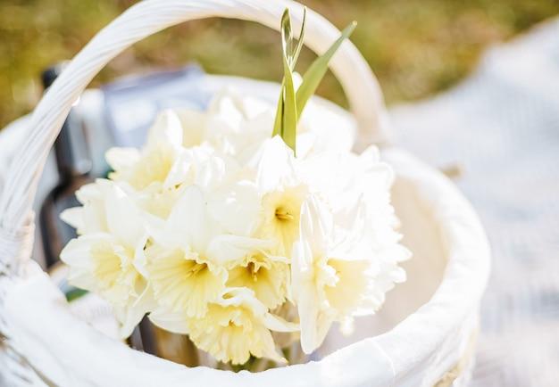 Gele bloemen narcissen boeket in een witte mand op een picknick in de lentetuin