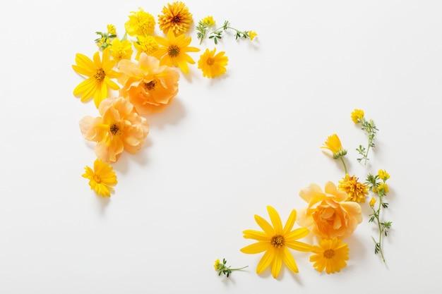 Gele bloemen op de witte muur