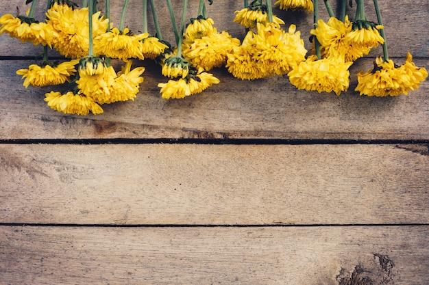 Gele bloemen van boeket, bovenaanzicht op houten achtergrondstructuur met kopie ruimte