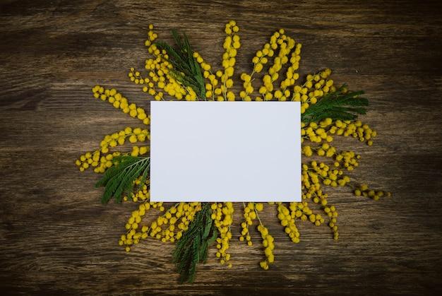 Gele bloemen van mimosa ingericht in de zon met een briefkaart op een houten achtergrond