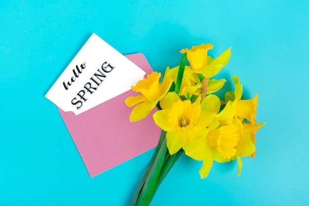 Gele bloemen van narcissen en roze envelop op een blauwe achtergrond flat lag