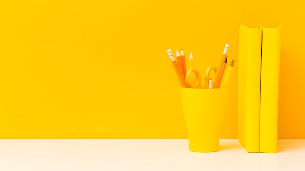 Gele boeken en potloden vooraanzicht
