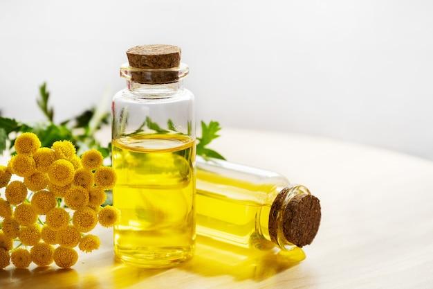 Gele boerenwormkruidolie in flesjes met een bloem