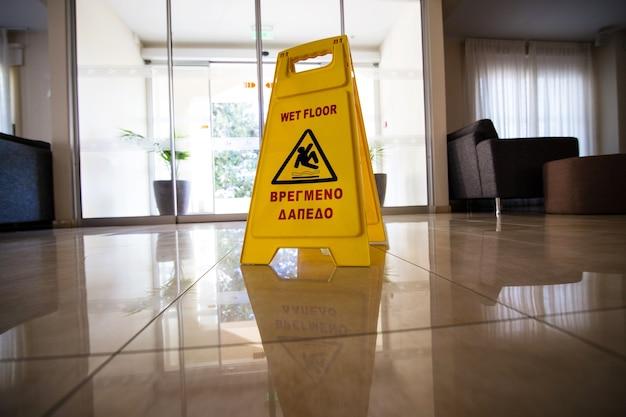 Gele bordwaarschuwing over natte vloer