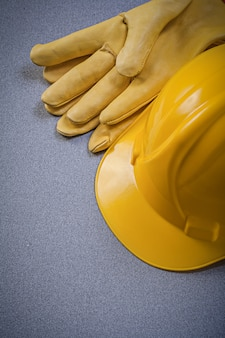 Gele bouwvakker en lederen beschermende handschoenen op grijs oppervlak