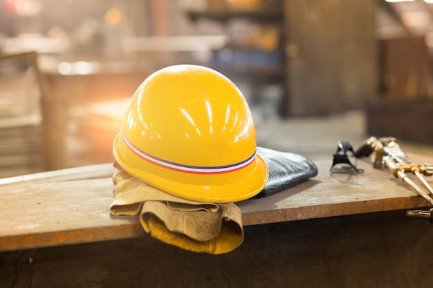 Gele bouwvakker en oude lederen handschoenen