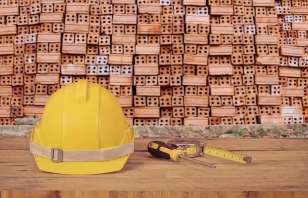 Gele bouwveiligheidshelm op hout