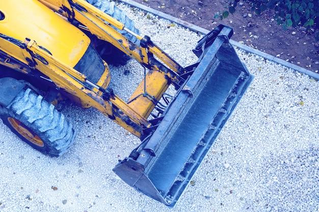 Gele bulldozer, laden grind voor wegenbouw