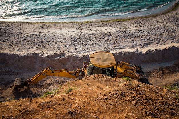 Gele bulldozer op de achtergrond van de heldere blauwe lucht en de kust.