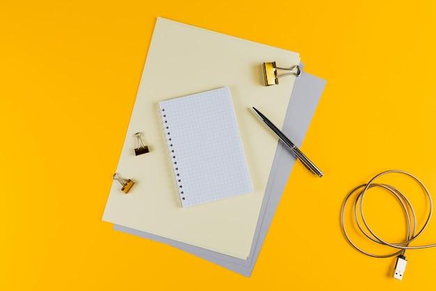 Gele bureaulijst met leeg notitieboekje en andere kantoorbenodigdheden. bovenaanzicht met kopie ruimte, plat leggen.
