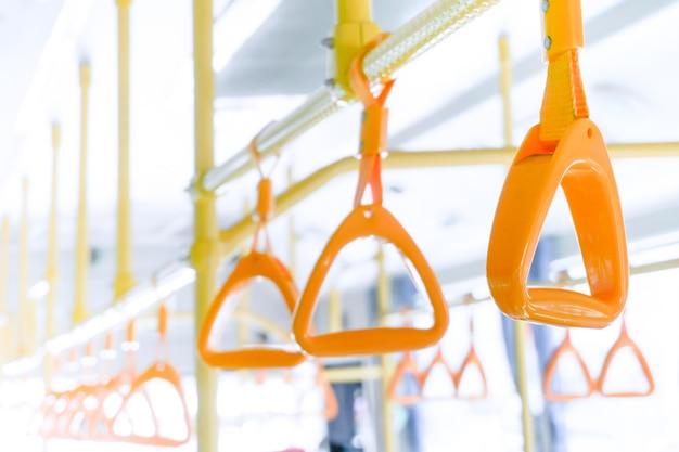 Gele busgreep aan plafond voor staande passagier