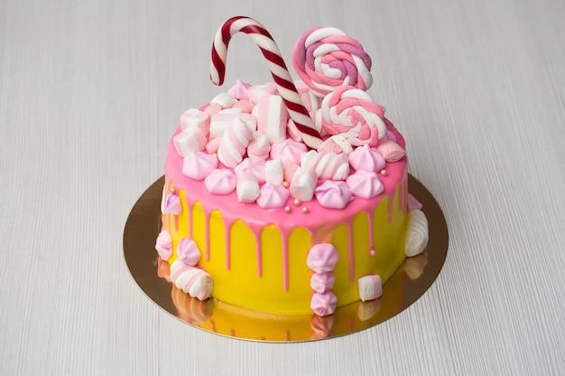 Gele cake voor kinderen met roze glazuur, meringue en snoep