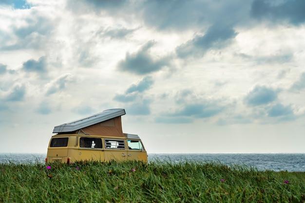 Gele camper staat voor de zee op een klif met dramatische lucht.