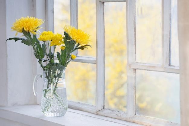Gele chrysant in glazen kruik op vensterbank